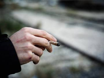 A close-up of a man's hand, holding a joint