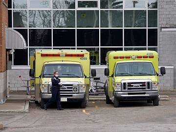 A paramedic wearing a face mask stands next to two ambulances