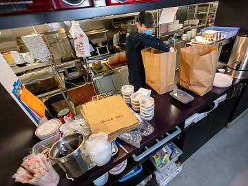 Masked restaurant worker prepares take-out food orders
