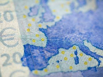 Close-up of Euro bill and map of Europe