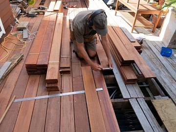A man kneels as he works with decking boards on a patio