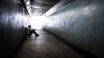 A homeless young man sits on the ground, in a tunnel