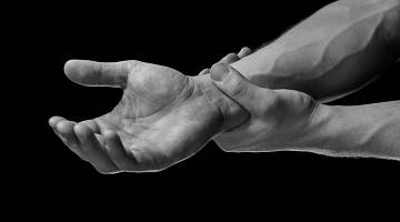 A close-up black and white photo showing hand and wrist in pain