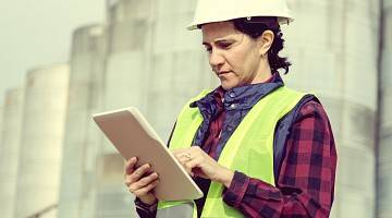 A young female engineer on a construction site is reviewing a document