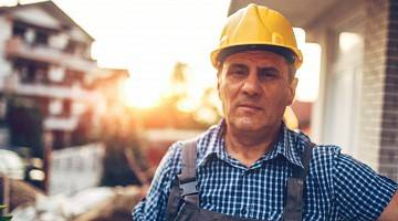 An older construction worker in a hard hat looks at the camera