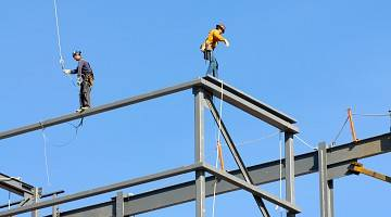 Two ironworkers walking on steel beams against a blue sky
