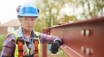 A female construction worker stands next to a steel girder