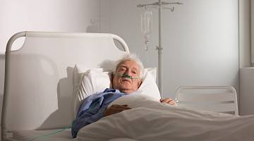 An elderly patient lying in bed