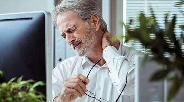 A businessman sits in his office in front of his computer, rubbing his neck in pain