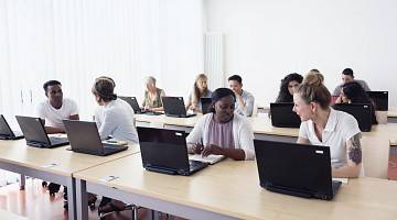 Diverse group of adults sit at laptops in training room