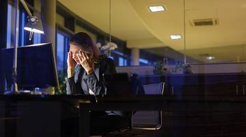 A tired worker holds her head in her hands as she sits at her desk in a dark office