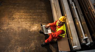 A helmeted worker sits on bench with laptop