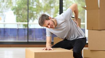 Male worker who is moving boxes holds his back in pain