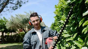 Young landscaping worker holds hedge trimmer