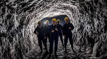 A group of workers in yellow safety helmets stand in an underground mine