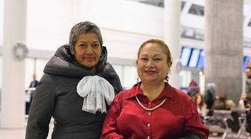 Two smiling women at the airport