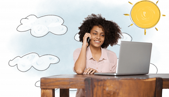 A smiling woman talks on the phone at her desk, with the sun shining behind her
