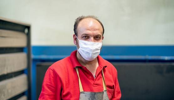 A worker wearing an apron and a cloth facial mask