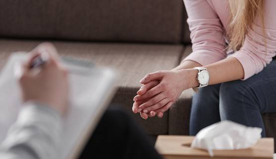 Close-up of two pairs of hands, belong to a counsellor and a patient sitting on a couch