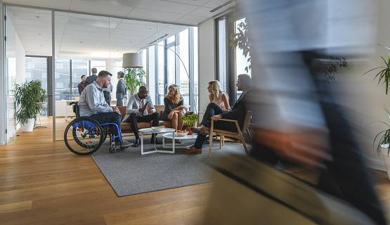 A worker in a wheelchair sits with colleagues in a busy office