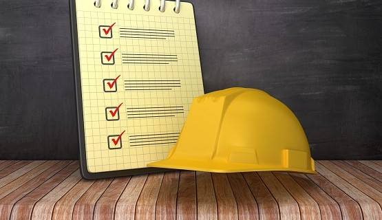 A hard hat, placed next to a check list, against a black background