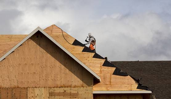 A lone roofing worker sits perched on top of a new being built