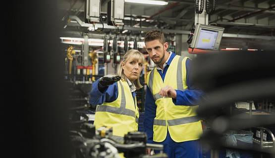 Two workers in safety vests, in a factory environment, point to something offscreen