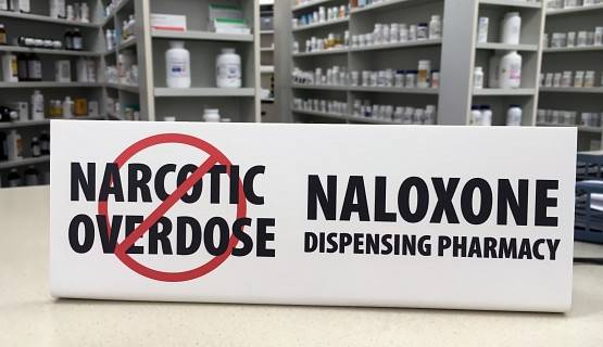 A sign for naloxone on a pharmacy counter