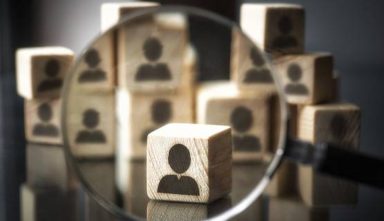 Silhouettes of people on cube wooden dice-size boxes, with magnifying glass focusing on one among them